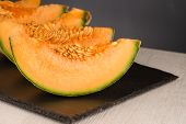 picture of honeydew melon  - Juicy honeydew melon on a black slate tray - JPG