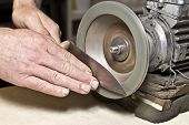 foto of friction  - sharpening knife process in a kitchen by a man - JPG