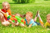 Постер, плакат: Children play with water guns on a meadow