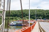 picture of pontoon boat  - tug boat sets section of pontoon bridge on the river Oka  - JPG