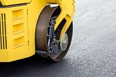 pic of paved road  - Yellow road roller leveling new asphalt on road - JPG
