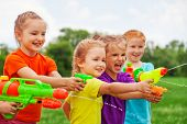 Постер, плакат: Kids play with water guns on a meadow