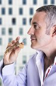 picture of mullet  - A man samples the smell of a mullete of cologne or perfume - JPG