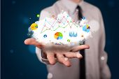 picture of presenter  - Young businessman presenting cloud with charts and graph icons and symbols - JPG