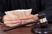 image of courtroom  - Midsection of male judge counting money at desk in courtroom - JPG