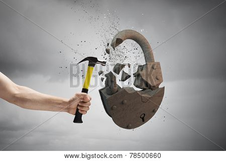 Close up of hammer in human hand breaking stone lock