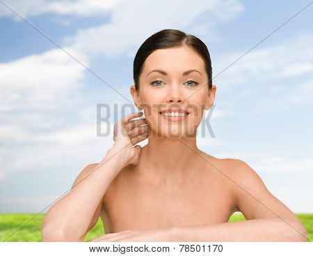 beauty, people and health concept - smiling young woman with bare shoulders over blue sky and grass background
