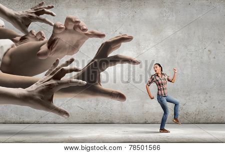 Young woman in casual running away from big hand