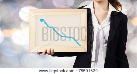 Young woman holding frame with increasing graph