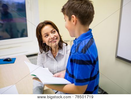 education, elementary school, learning, examination and people concept - school boy with notebook and teacher in classroom