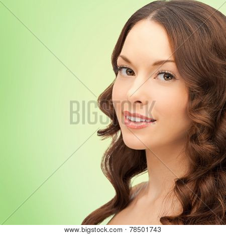 beauty, people and health concept - beautiful young woman with bare shoulders and long wavy hair over green background