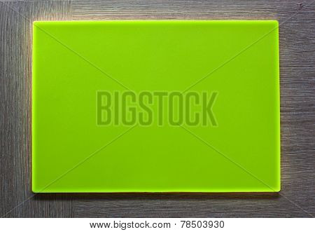 New green plastic plate with empty textspace on wooden background.
