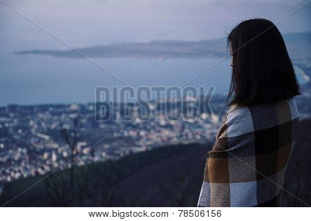Woman Wrapped In Plaid Looking At The City In Night