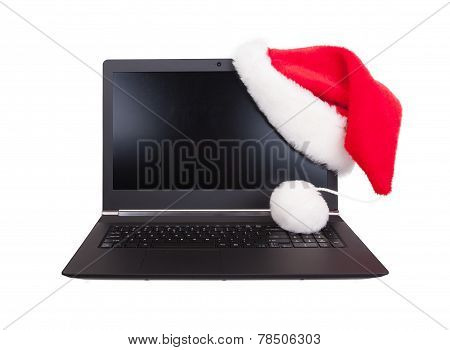 Modern Open Laptop With Red Santa Claus Hat Put On Lcd Corner