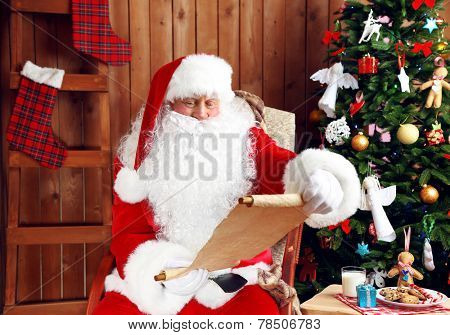 Santa Claus with list of presents sitting in comfortable rocking chair near Christmas at home