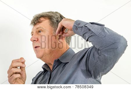 Serious Man In Shirt Handling His  Hearing Aid