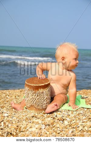 funny kid Drumming on the beach