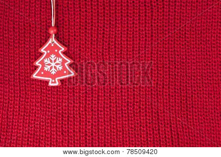 Christmas fir tree decoration on red wool knitted fabric background