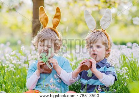 Two Little Friends With Easter Bunny Ears And Eating Chocolate