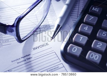 Calculator, Glasses And Pen On Invoice Papers