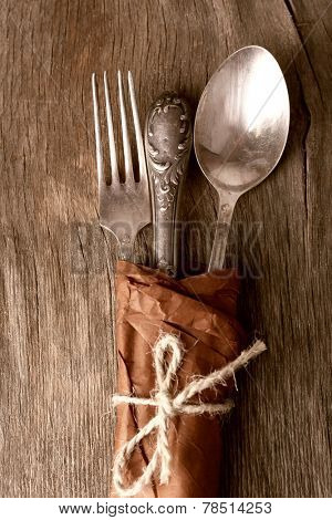 Tableware wrapped in paper on wooden background