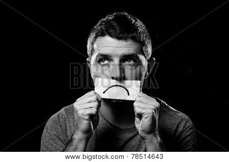 Young Depressed Man Lost In Sadness And Sorrow Holding Paper With Sad Mouth In Depression Concept