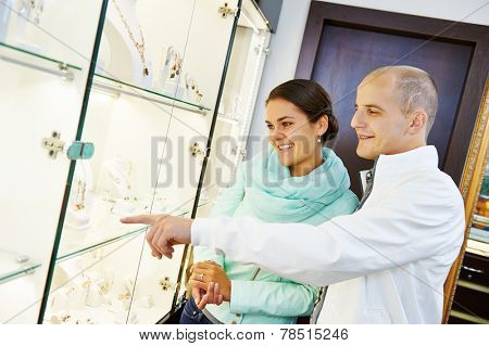 Young happy couple together selecting gift at jewelry boutique shop