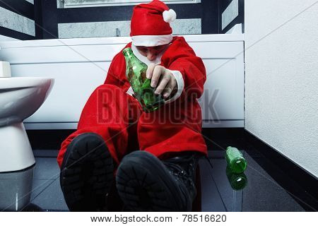 Drunken Santa Claus Sleeping At Bathroom With Beer Bottle In Han