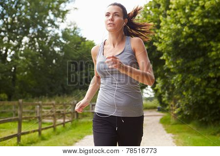 Woman Running In Countryside Wearing Earphones