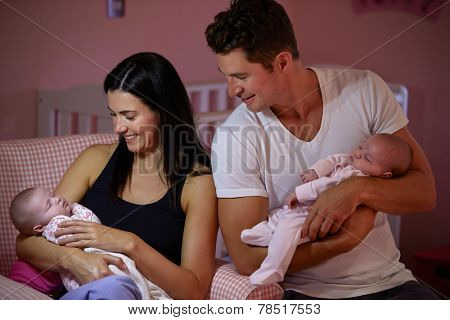 Parents At Home Cuddling Twin Baby Daughters In Nursery