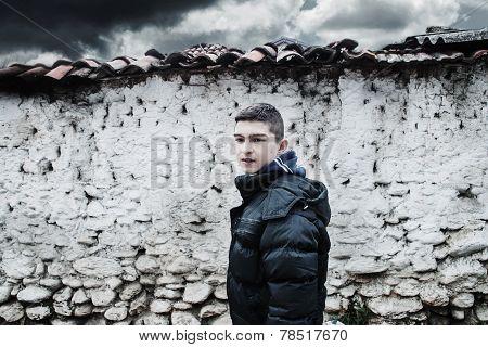 sad young boy before loam wall