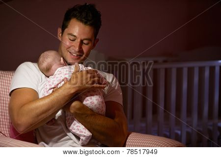 Father At Home Cuddling Newborn Baby In Nursery