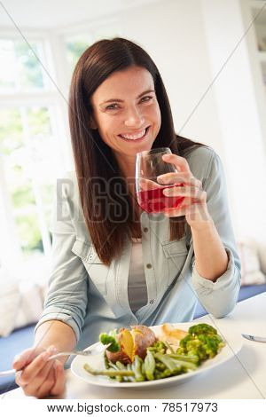 Portrait Of Woman Eating Healthy Meal In Kitchen