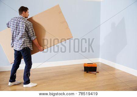 Man Preparing To Assemble Flat Pack Furniture