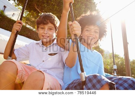 Two Girls Boys Fun On Swing In Playground