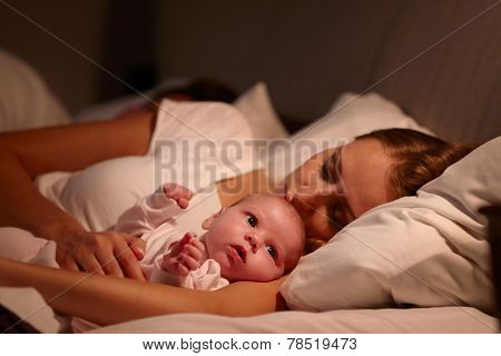 Parents Sleeping In Bed With Newborn Baby