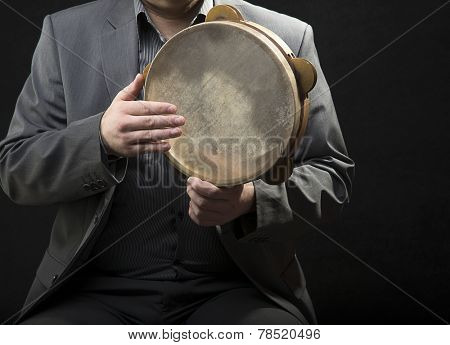Tambourine player over black background with space for your text