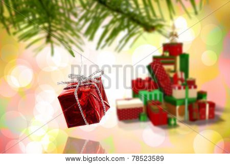 Red christmas decoration hanging from branch against girly pink and yellow pattern