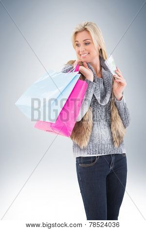 Blonde in winter clothes holding shopping bags on vignette background