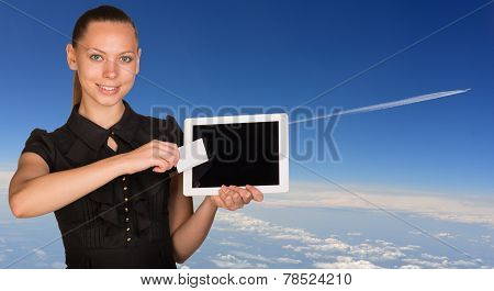 Beautiful businesswoman holding tablet PC and business card in front of screen. Blue sky with clowds