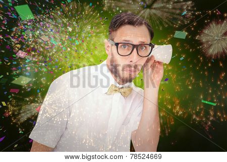 Geeky businessman eavesdropping with cup against colourful fireworks exploding on black background