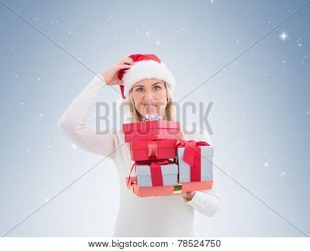 Confused blonde in santa hat holding gifts on vignette background
