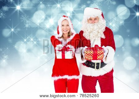 Santa and Mrs Claus smiling at camera offering gift against shimmering light design on blue