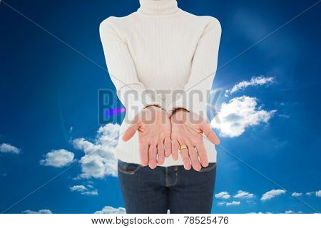 Woman standing with her hands out against cloudy sky with sunshine