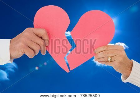 Couple holding a broken paper heart against bright blue sky with clouds