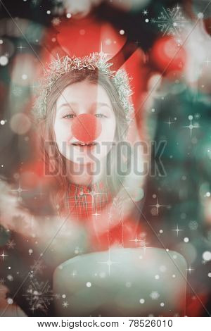 Festive little girl wearing red nose against candle burning against festive background