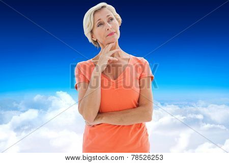Thinking older woman with arms crossed against blue sky over clouds