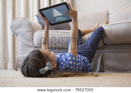 Little girl using digital tablet in the living room against merry christmas message