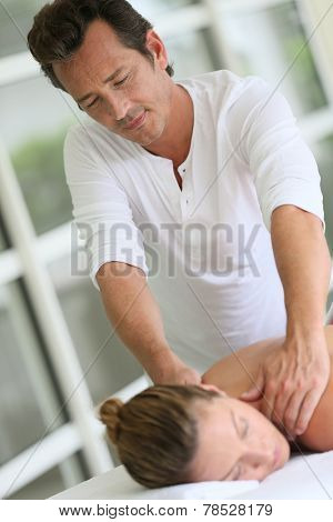 Masseur in spa institute doing massage to woman
