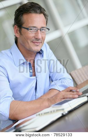 Businessman with eyeglasses working on laptop computer